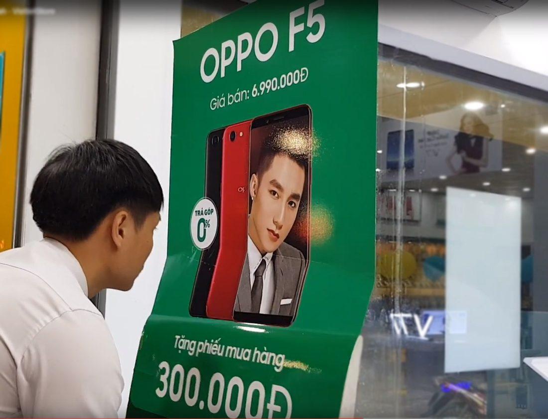 Dán poster trong cửa hàng điện thoại
